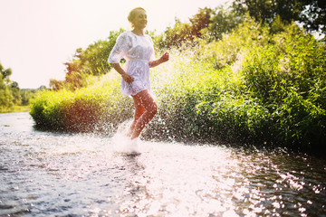 Young woman running in shallow water. Summertime.