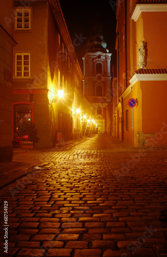 A church and cobbled street at night in Poznan .