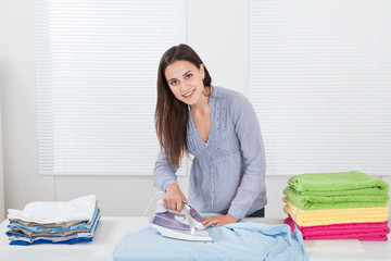 Woman Ironing Clothes In House