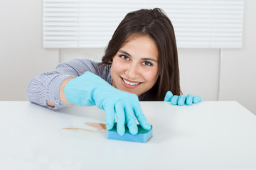 Hand Cleaning Dirt On Table With Sponge