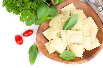Homemade pasta ravioli with fresh basil, isolated over white bac
