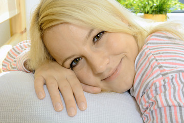 Frau im Pyjama liegt erholt auf Bett-Kissen
