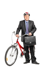 Mature businessman posing in front of a bike