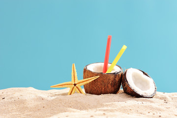 Exotic cocktail in a coconut shell on a sandy surface