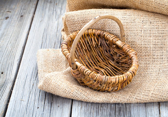 Empty wicker basket on the wooden background