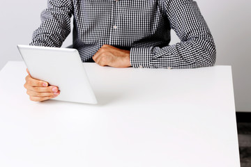 Man sitting on the table and holding tablet computer