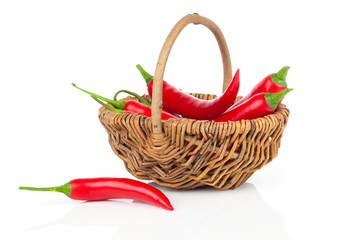 Red chili pepper in a wicker basket, isolated on white backgroun