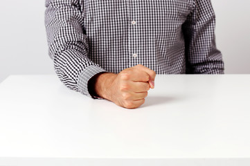 Closeup image of fist on a white table