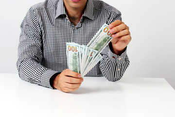 Midsection of businessman holding banknotes at desk