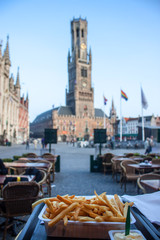 Typical belgian meal - frie; Bell Tower in Bruges. Shallow DOF.