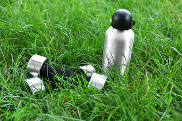 Dumbbells and bottle with water on green grass background