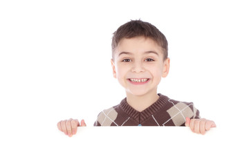 Young boy hiding behind a billboard and making a face on camera