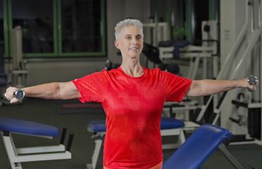 Reife Frau im Fitness Studio beim Kurzhantel Training