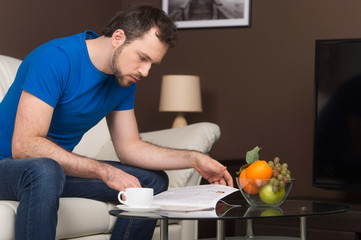 Man sitting on sofa in home and reading.