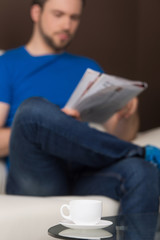 Man sitting on sofa relaxed and reading.