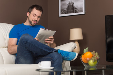 Man sitting on sofa relaxed and smiling.