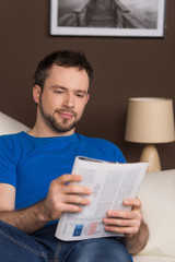 Man sitting on sofa relaxed and reading magazine.