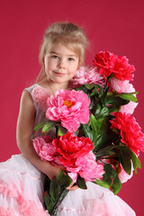 little girl dressed as a ballerina with a bouquet of peonies on