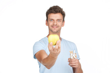 young man stretching out hand with apple.