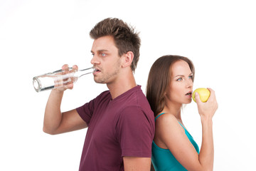 young man and woman with water and apple.