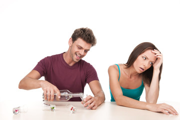Man pouring alcohol and woman sitting upset at table.