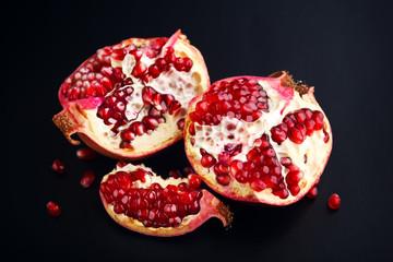 Ripe pomegranate fruit on black background