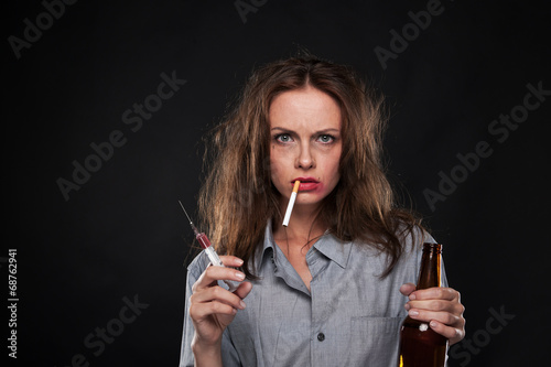 portrait of woman smoking cigarette hanging out of her mouth.