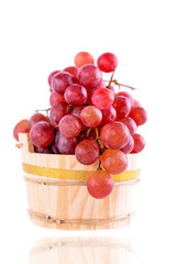 Red grapes in a rustic wooden bucket