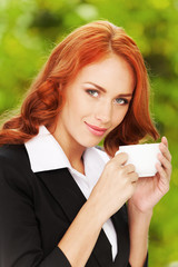 Redhead business girl with cup of tea.