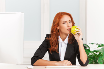 Young businesswoman eating apple at work.
