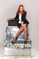 business woman sitting on suitcase full of money.