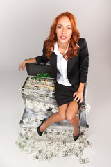 top view of woman sitting on suitcase full of money.