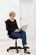 junge frau im leeren büro mit laptop