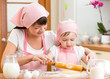 Mother and kid prepare cookies using a rolling pin