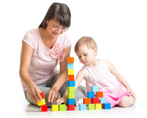 kid girl and her mom play with building blocks