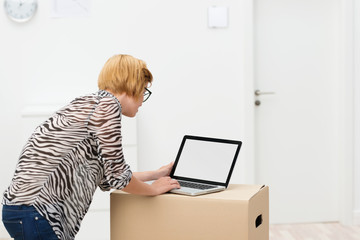 frau beim umzug schaut auf laptop