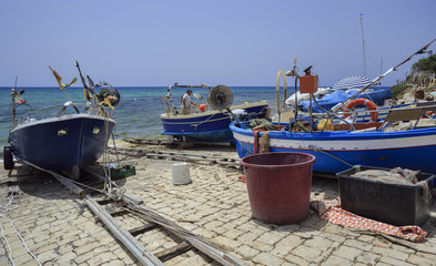 Italy, Sicily, fisherman working ashore on his fishing boat