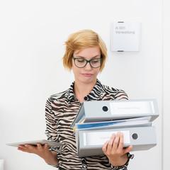junge frau im büro trägt akten und ein tablet