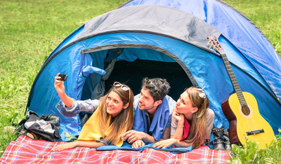 Group of best friends taking a selfie at camping tent