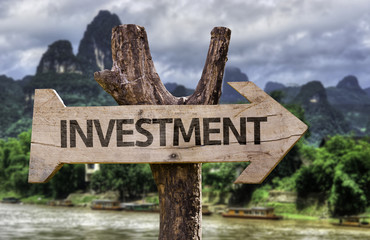 Investment wooden sign with a forest on background