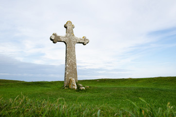 Ancient cross surrounded of green grass