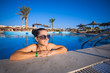 Woman relaxing in blue swimming pool
