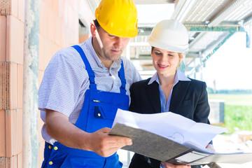 Team kontrolliert Bau Pläne auf einer Baustelle