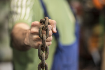 Man making streght against a chain