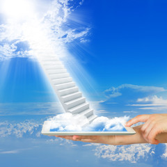 Hands hold tablet pc with stairs in sky
