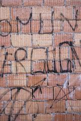 Muro di mattoni con scritte e graffiti