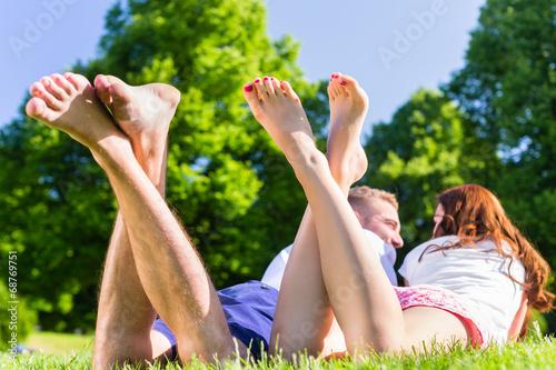 canvas print picture Freunde halten im Park die Beine in die Sonne