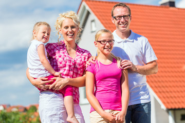 Familie steht stolz vor Haus