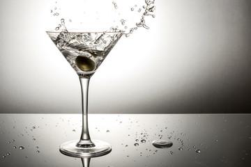 Olive splashing on martini