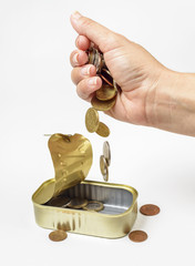 Female hand pour down coins into fish can